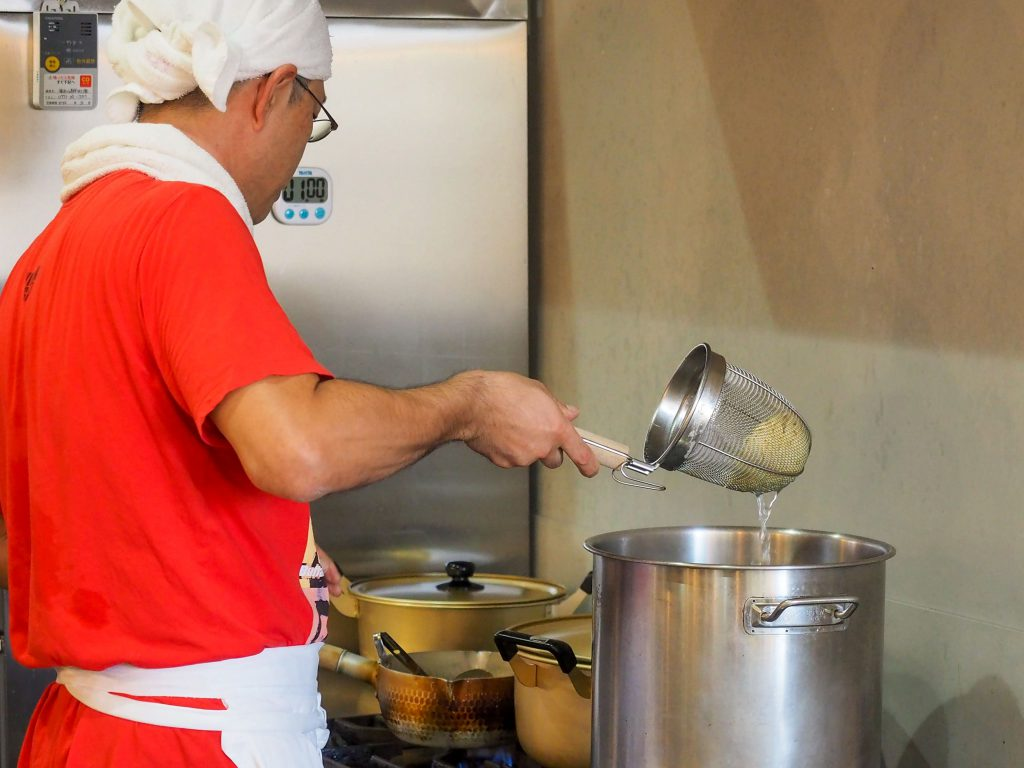 吉見製麺所の店主がラーメンを茹でるシーン